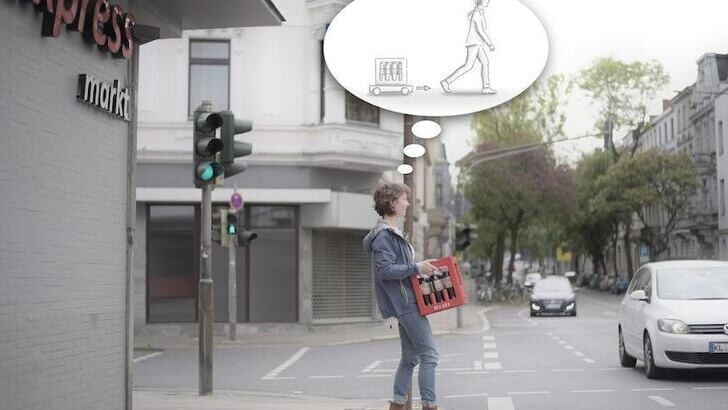 Woman at traffic lights carries a drinks box